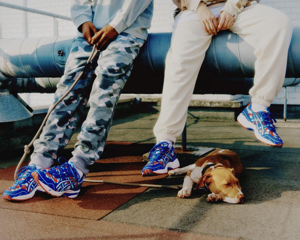 Deux jeunes adultes portant la Asics GEL-1090 X Bape, coloris : CAMO FRANCE en compagnie de leur chien, sur les toits de Paris.